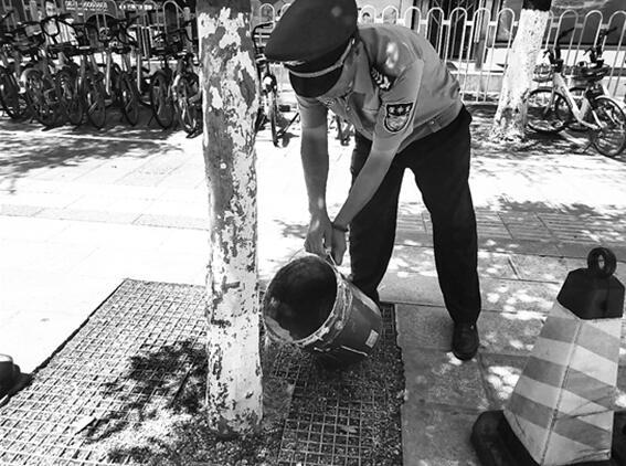 在张老师带动下,银行保安也给行道树浇水。记者左学佳摄