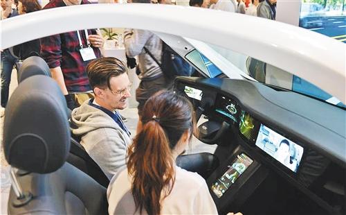 参观者在2019国际显示周上体验京东方柔性显示屏带来的智慧驾驶。(资料图片)