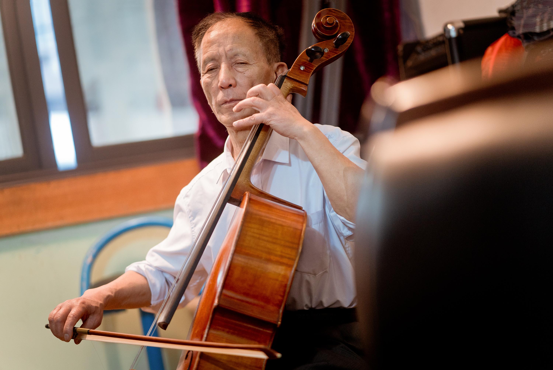 """""""自强不息艺术团""""65岁的大提琴手冯潜正在排练乐队原创曲目《川剧弹戏曲牌联奏》。"""