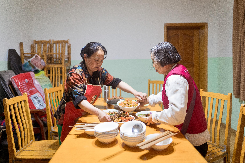 乐队排练日,乐队发起人张世维的爱人冯懿萍(左)和其他盲人家属志愿者黄中林(右)一起给乐队准备免费午餐,每次都是6菜一汤。