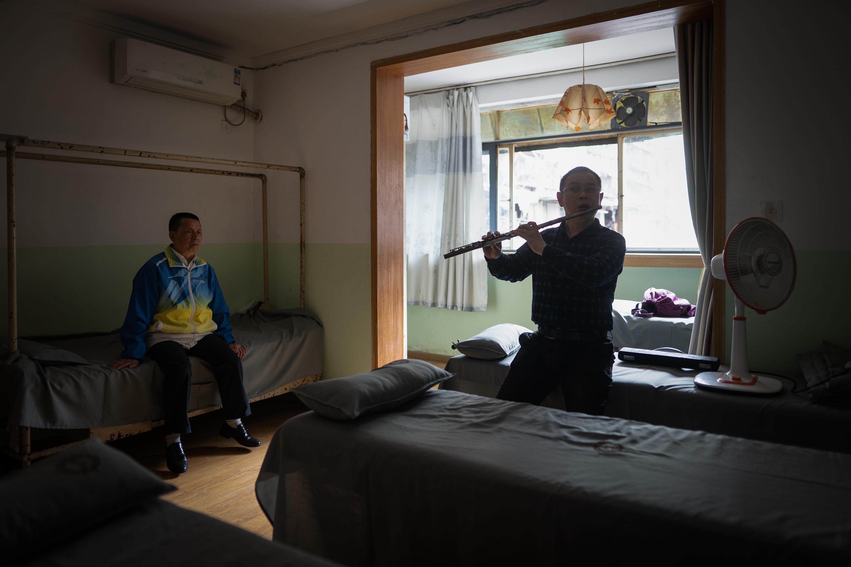 盲人互助按摩院内,张世维和乐队长笛演奏者邵岳平,一起练习新曲目。张世维本身不会乐器,他的身份更像是乐队的保姆兼经纪人,组织排练、保障后勤、联系演出都是他在负责。