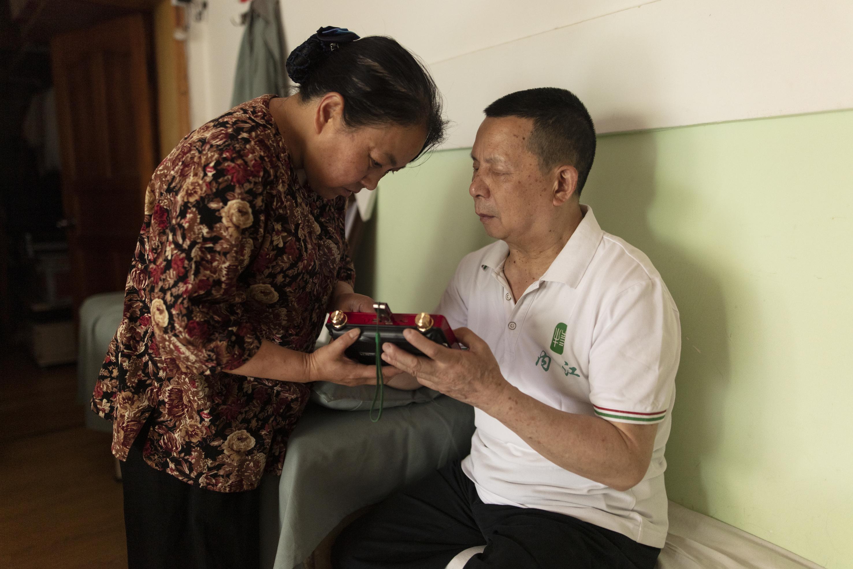冯懿萍帮助张世维在播放机器上听乐队上次演出的视频资料,现在冯懿萍就是张世维的眼睛,照顾他日常起居、照顾乐队排练,收集整理乐队资料,对外沟通。