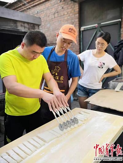 任晓猛、任文亚夫妻正在自家租住的小院里教授学员如何切面。中国青年报·中国青年网记者邢婷/摄