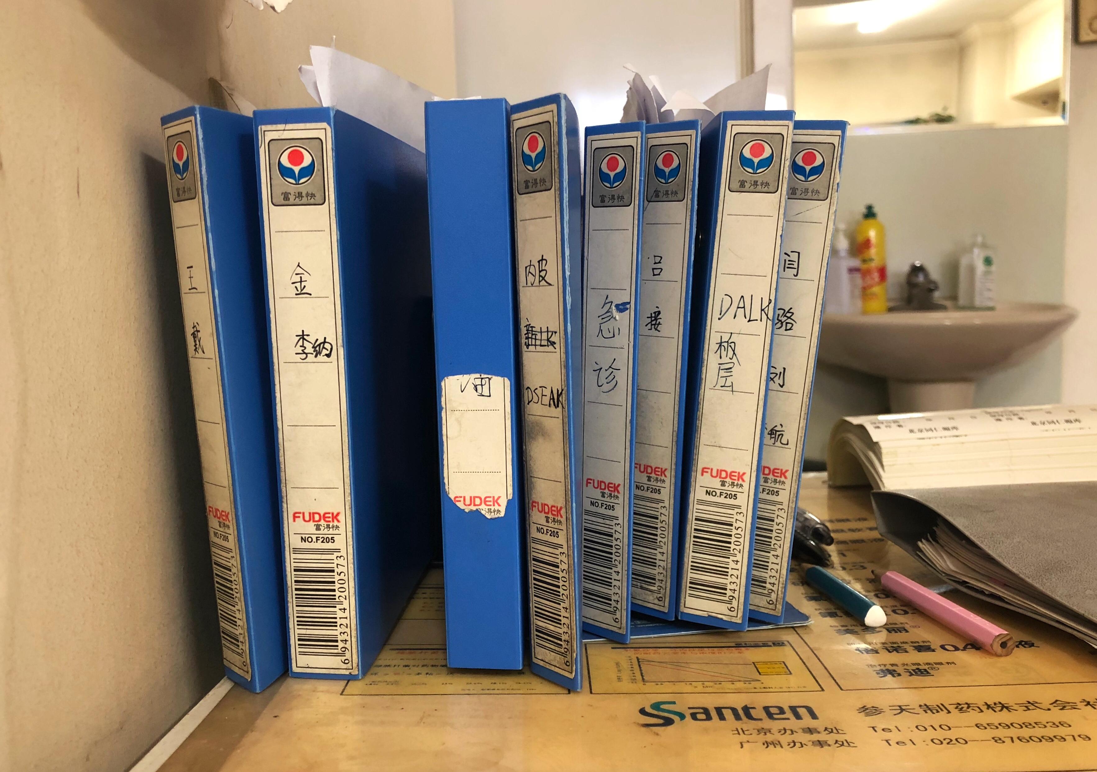 (图片拍摄于于津办公室,桌上排列的蓝色文件夹中存放着等待做角膜移植手术的患者病历。苏悦/摄)