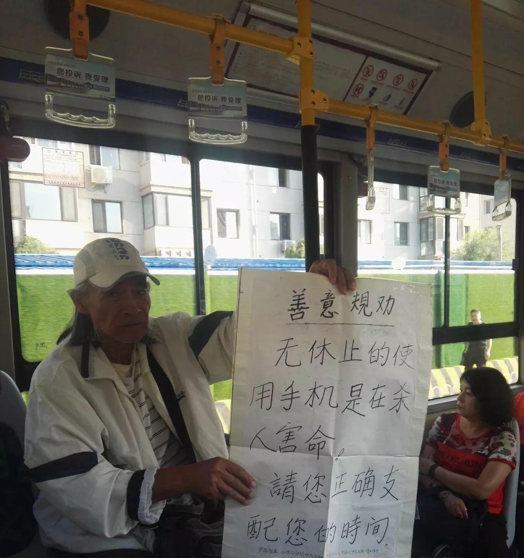 沈阳75岁大爷坐公交举宣传牌:无休止使用手机是杀人害命