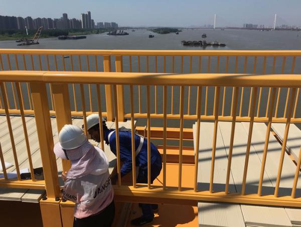 武汉杨泗港大桥的夫妻档工人:高温下衣服湿了又干,干了又湿