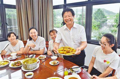 正在上菜的黄彭勋(右二)热情地向客人介绍农家乐传统手工特色菜——?#33073;温?#26524;。 陈斌荣摄