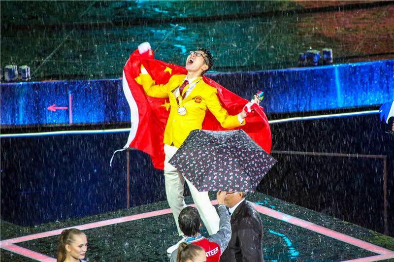 身披国旗的徐澳门跃上领奖台,雨水和泪水模糊在一起。人力资源和社会保障部供图