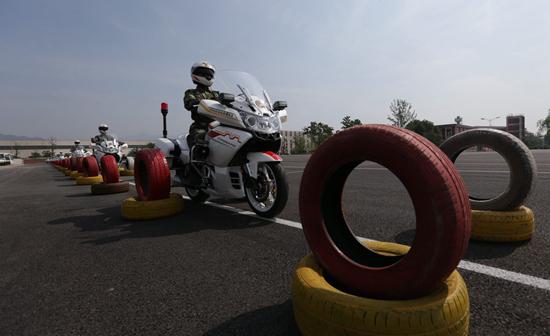 国宾护卫队员驾驶摩托车通过宽1.1米、长100米的轮胎通道。