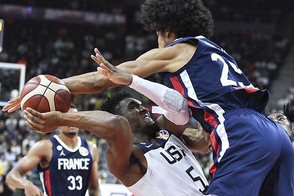 美国队球员米切尔(下)在比赛中突破法国队球员拉贝里的防守。