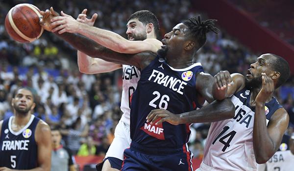 法国队球员莱索尔(中)在美国队球员哈里斯(左)和米德尔顿的包夹下拼抢篮板球。