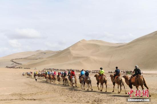游客骑骆驼在敦煌鸣沙山月牙泉景区游览,驼队宛如长龙。 中新网资料图