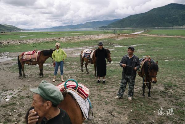 2019年8月1日,香格里拉帕纳海岸边,当地村民牵着马匹等待游客生意。该地未被划入国家公园试点范围,这里的马帮还在继续经营。