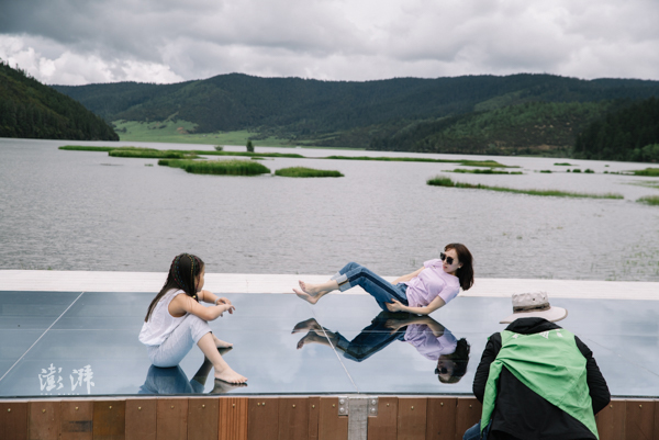 2019年7月31日,属都湖岸边,游客在公园搭建的平台上拍照。