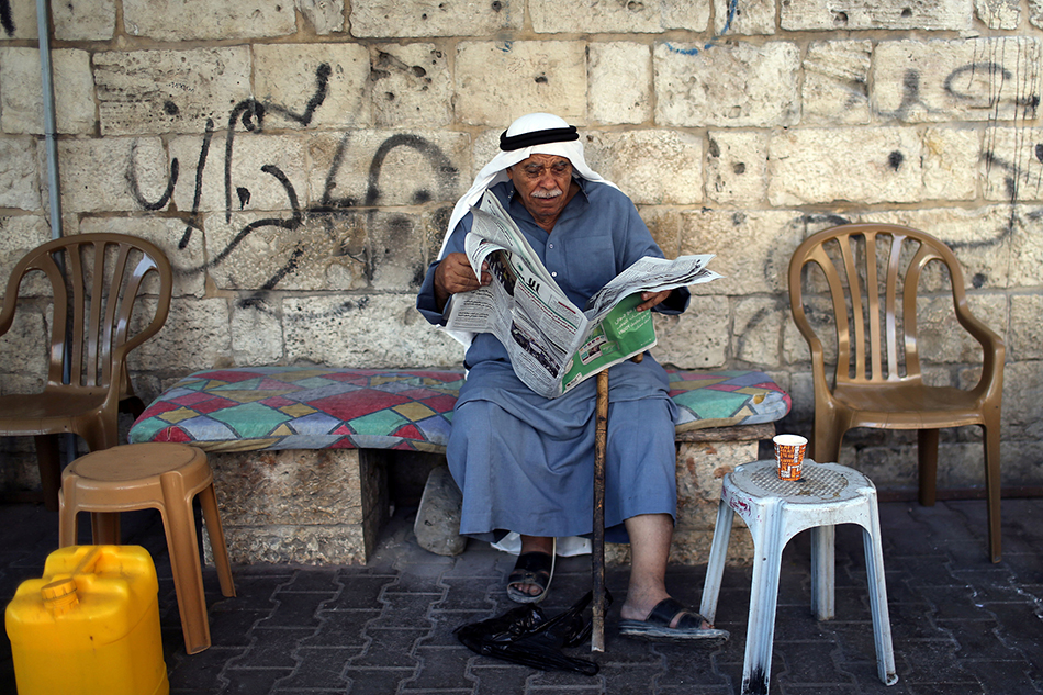 当地时间2019年9月18日,加沙地带,一名巴勒斯坦男子正在阅读一份报道以色列议会选举新闻的报纸。 视觉中国 图