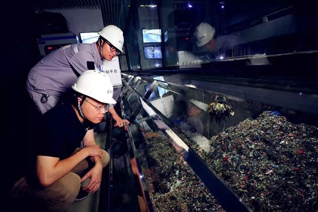 阿里工程师与瀚蓝工人在观察垃圾进料情况