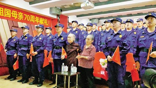 陈淑琼与消防队员一起收看大会直播 记者 丁洁 摄