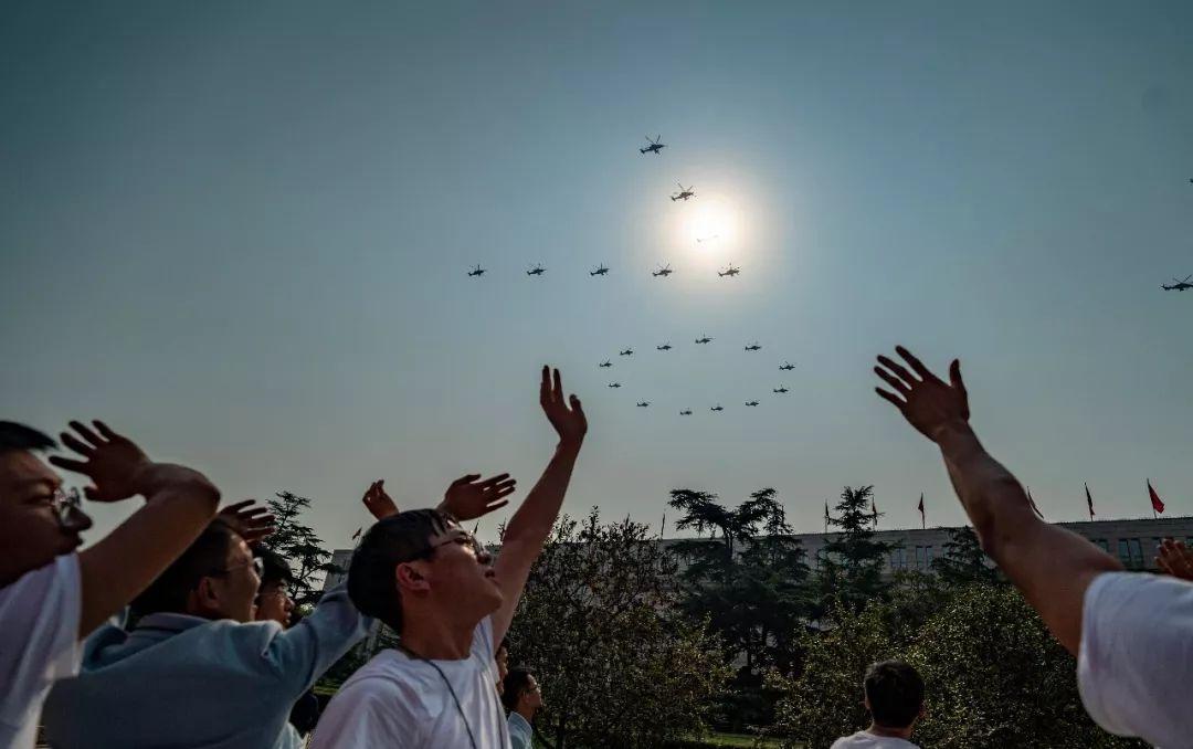 """这是群众向在空中组成""""70""""字样的20架直升机挥手致意。新华社记者江文耀 摄"""