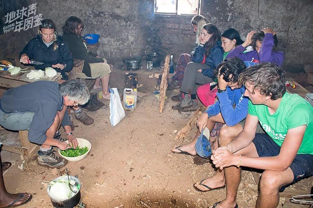 【下】雨【时】,【我】【们】借【用】营【地】旁边【的】【学】校厨房【来】做饭,【一】边讨论社区【活】【动】【的】安排,【一】边【在】屋【子】【里】围坐【着】,等待午饭。