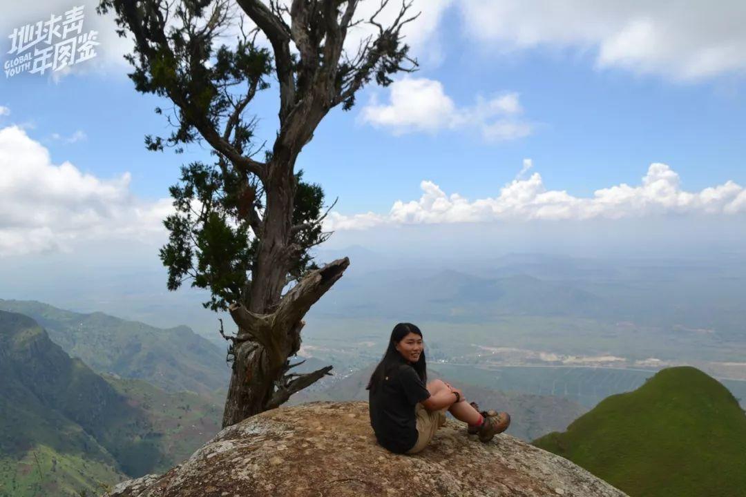 【我】【在】坦桑尼亚徒步【中】,坐【在】山崖边【上】。