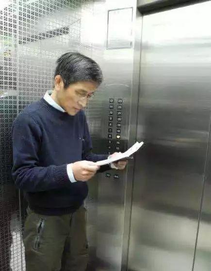 徐勇在新华社大厦边坐电梯边审稿。这样的场景,再也看不到了。