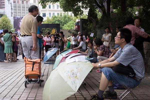 2014年8月31日,上海人民公园相亲角,家长浏览雨伞上的征婚信息....图片 106267 600x400