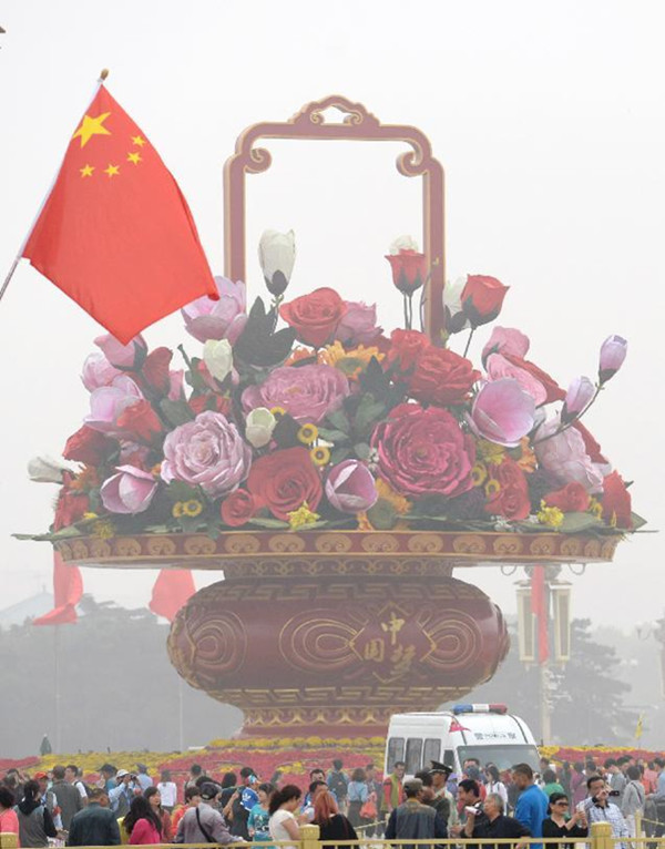 今年的天安门广场国庆花坛主景花篮为巨型花艺作品,透露出浓浓的中国风,突出体现中华文化的深厚底蕴。大花篮篮体增加了中国结图案,四周都嵌有中国梦字样。花材主要选用牡丹、月季、玉兰、芙蓉、向日葵等,这些花材,里面都是金属结构,外面是经过处理的织物。其中牡丹最大,直径3.