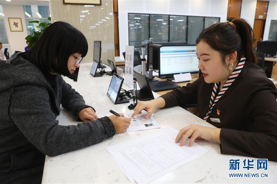11月23日,在辽宁沈抚新区政务服务中心,工作人员(右)协助办事人办理业务。新华社记者 龚兵 摄