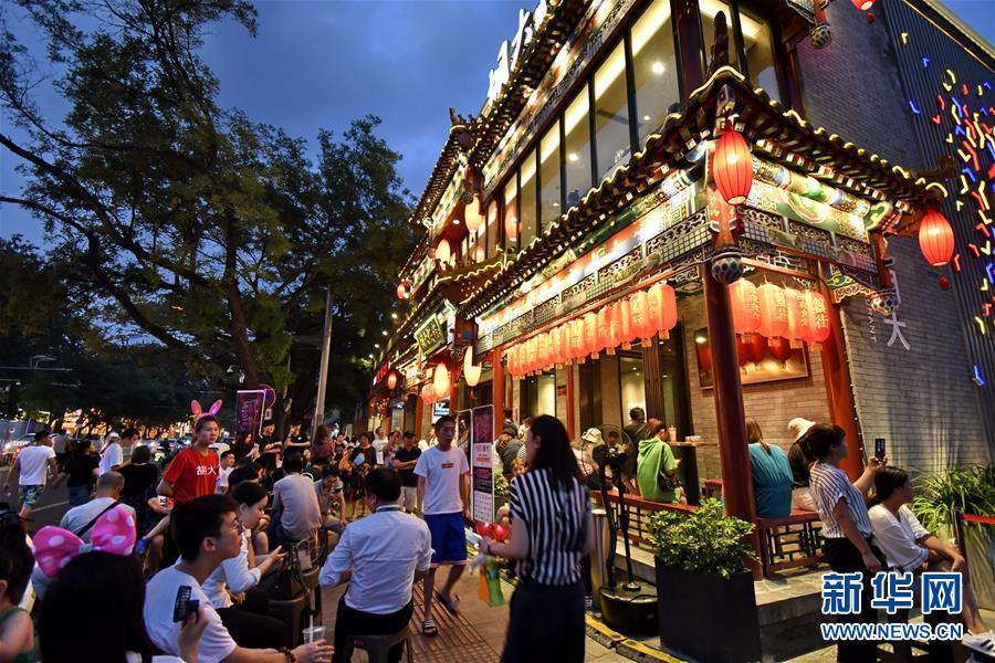 8月7日,人们在北京东城区簋街的餐饮店外等候吃夜宵。新华社记者 李欣 摄