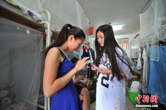 资料图:女生在寝室用手机选修课程。 中新社记者 胡雁 摄