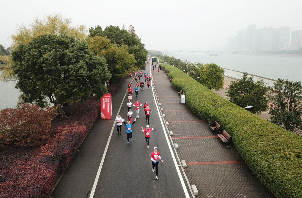 2019年12月26日,长沙红色半程马拉松在长沙市橘子洲景区开跑,参赛选手在比赛中。(无人机拍摄)新华社发(陈振海摄)