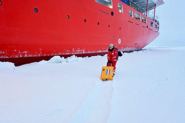 科学家杰西·克莱米恩正把一台可移动的气溶胶采样器搬到冰上,试验其在严寒条件下的性能。