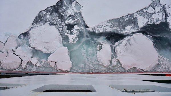 """""""费德洛夫院士号""""穿过北冰洋浮冰群的南缘,巨型冰块在船身旁漂过。"""