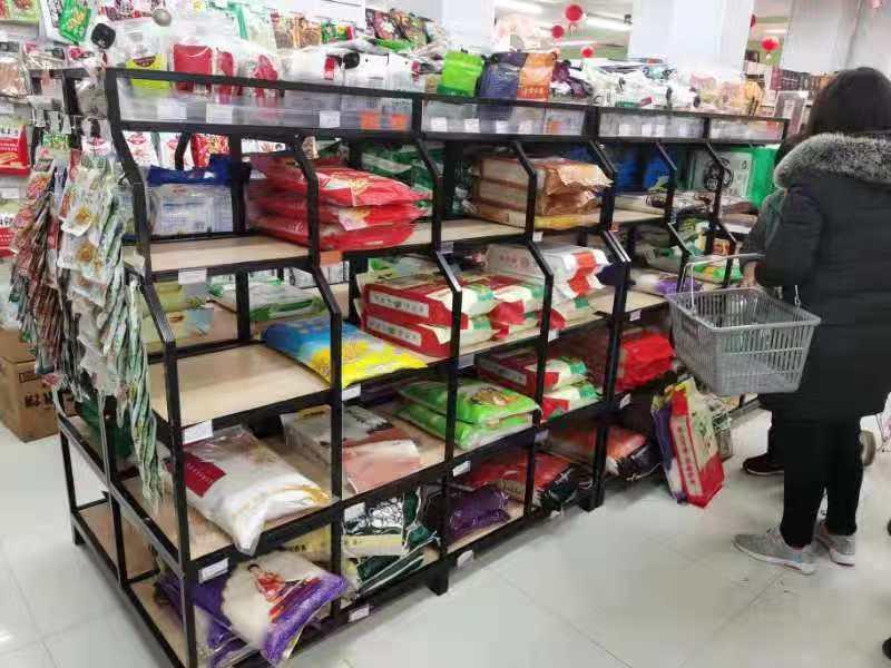 """李晓""""封城""""后在超市采购,货架上的米袋数量已不多。"""