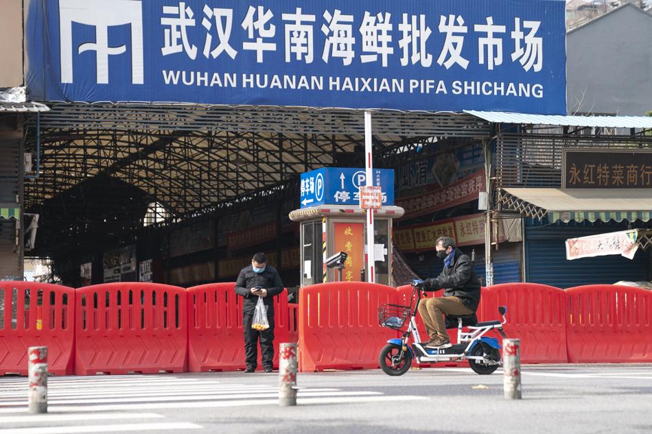目前抗疫进入攻坚战时期,也是加强信息治理的关键期。图为1月29日,武汉市民经过已经被封闭的武汉华南海鲜批发市场。 新华社 图