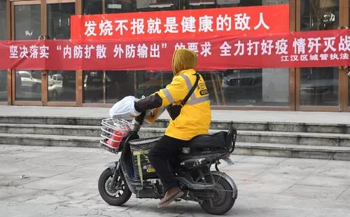 """大排查武汉打响抗""""疫""""保卫战。2月9日,一位快递员在武汉市江汉区唐家墩街西桥社区送货。新华社记者程敏摄"""