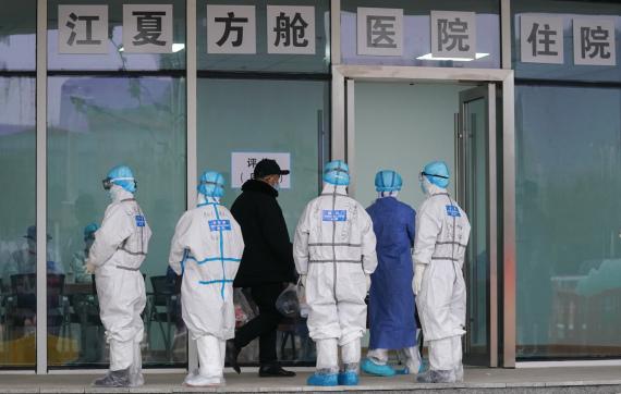 2月14日,武汉江夏方舱医院的医护人员在迎接前来入住的病人。 新华社 图