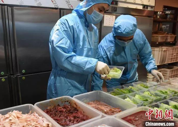 工作人员全副武装为线上下单的顾客打包菜品。