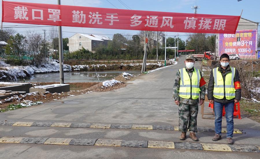 2月16日,在武漢市蔡甸區張灣街黃土坡村,村民志愿者在路口執勤,黃土坡村這個路口也是進出新民村的必經之路,兩個村子相鄰。? 新華社 圖
