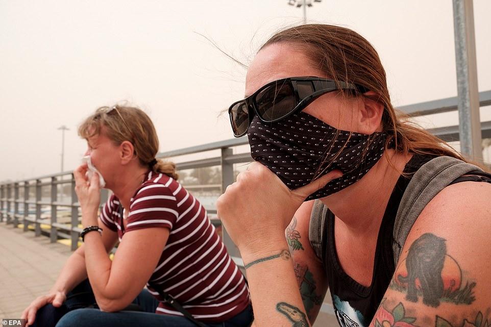 两名旅客在大加那利岛机场等候,戴上口罩免受沙尘侵扰 EPA图