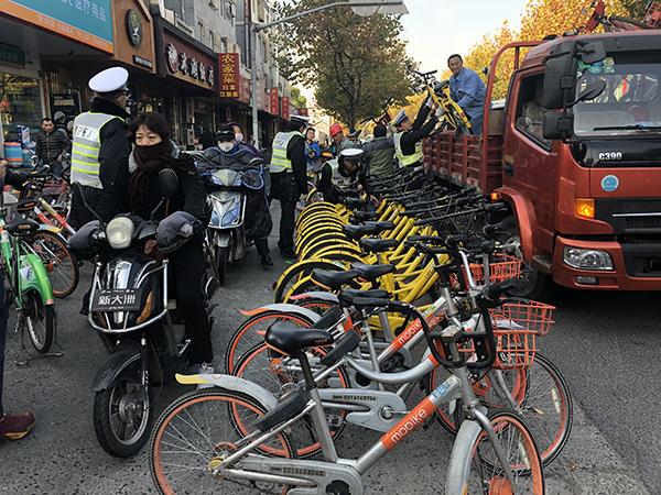 上海一条马路遭遇共享单车占道,交警和社区每天清理近三百辆